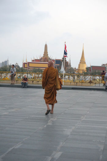 a monk walking toward The Emerald Buddha temple Ancient Architecture Bangkok Built Structure Culture Cultures Emerald Buddha Temple Famous Place History Monk  Place Of Worship Religion Spirituality Temple Temple - Building Thailand Tourism Travel