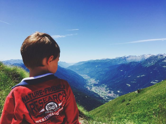 Mountain Childhood Boys One Person Day Real People Casual Clothing Mountain Range Leisure Activity Rear View Sky Standing Clear Sky Nature Lifestyles Beauty In Nature Outdoors One Boy Only Tree People Italy