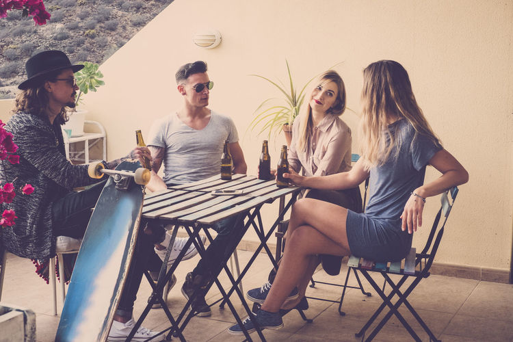 4 guys drink beer on the terrace Beautiful People Hat Vintage Filter Blond Hair Casual Clothing Chair Day Drink Drinking Friendship Full Length Leisure Activity Lifestyles Outdoors Real People Relaxation Sitting Table Terraced Field Togetherness Warm Colors Wood Table Young Adult Young Men Young Women