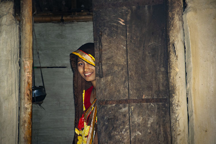 Smiling young woman wearing sari while peeking by door in house at village