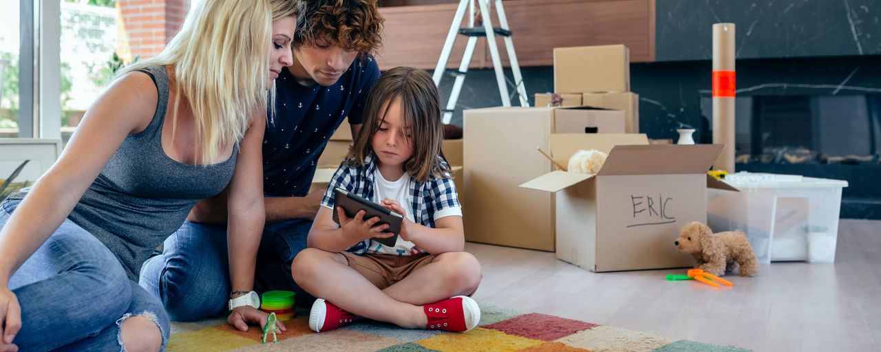 Parents supervising their little son playing the tablet sitting on the floor of the living room Family Fun Happiness Happy Horizontal Moving Tablet Unpacking Woman Apartment Boxes Boy Cardboard Home Interior House Indoors  Lifestyles Living Room Mammal New Home Packing Placing Real People Relocating Three People