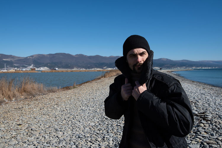 A young man walks on the beach. Seacoast in the background. One person in the frame. Man on the background of a clear sky. He is warmly dressed in boots, jeans, a sweater, a jacket and a hat. Casual wear. The guy wears a mustache and stubble. Hair out of the caps. Winter sunny day. Live photo. Lifestyles Lifestyle Authentic Moments Authentic Candid Real People One Person Sky Leisure Activity Water Clothing Clear Sky Day Nature Scenics - Nature Standing Front View Young Adult Mountain Black Color Beauty In Nature Warm Clothing Outdoors Obscured Face Hat