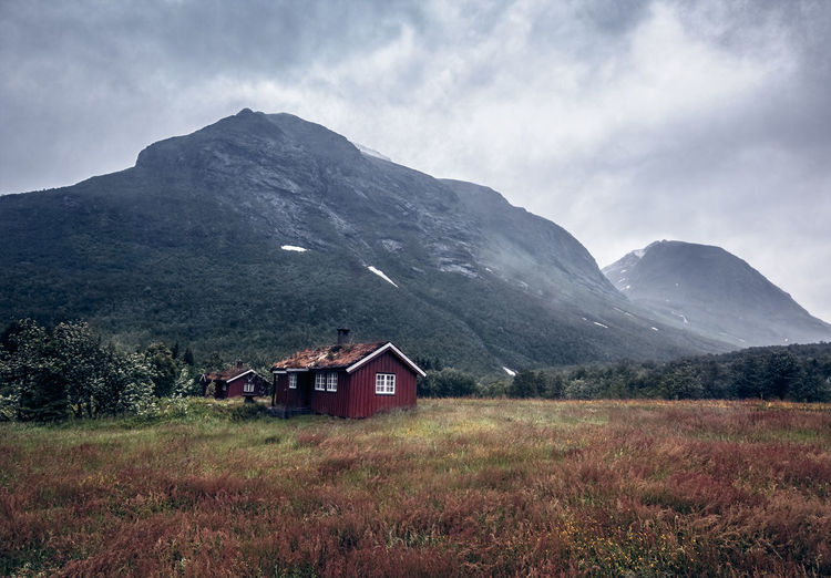 houses in front of a mountain EyeEm Best Shots Norway Architecture Beauty In Nature Building Exterior Built Structure Cloud - Sky Day Environment Field Grass House Land Landscape Mountain Nature No People Scenics - Nature Sky