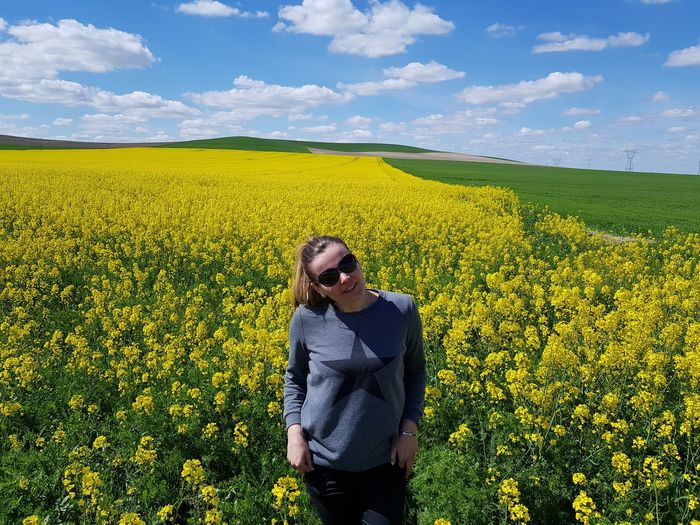 Woman standing amidst oilseed rape