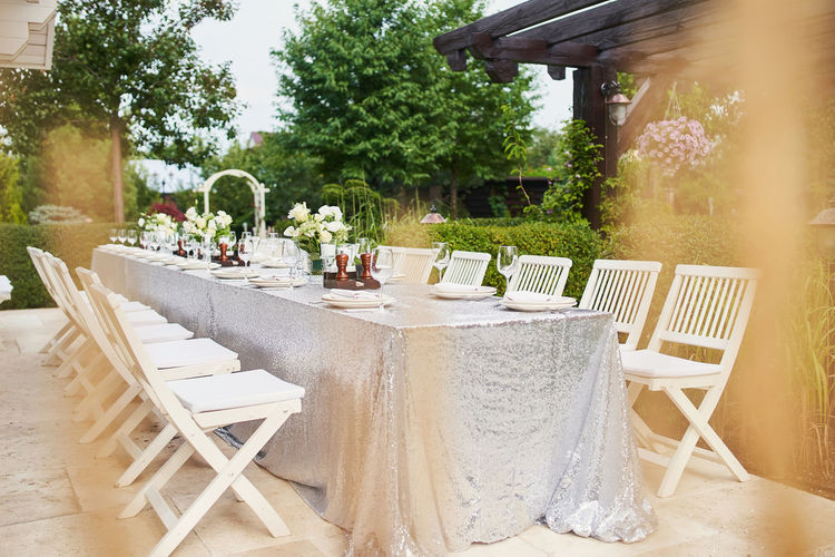 Empty chairs and table in yard