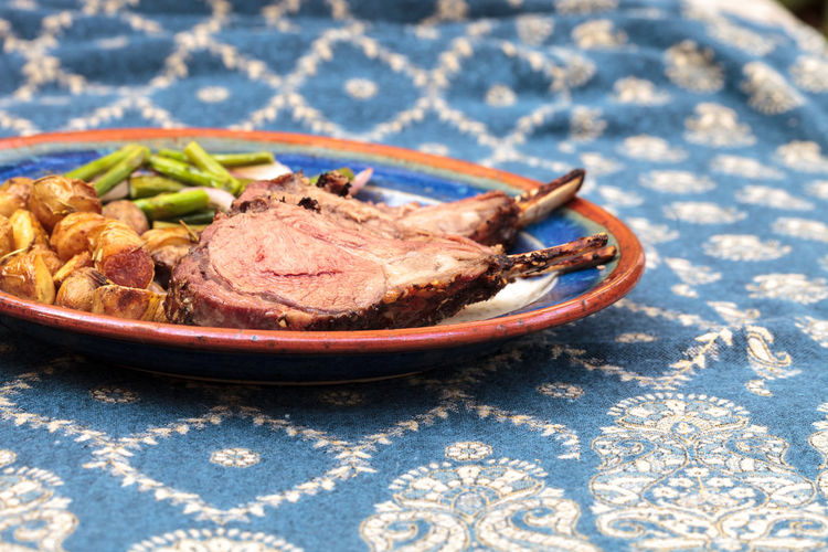 Rack of lamb with roasted golden baby potatoes seasoned with rosemary and sea salt and garnished with asparagus, onions and mushrooms on a dinner plate. A royal blue tablecloth is spread under the place setting. Asparagus Comfort Food Day Dinner Food Lamb Lamb Chops Meal Meat No People Ready-to-eat Rich Food Roasted Lamb Roasted Potatoes Rosemary Roasted