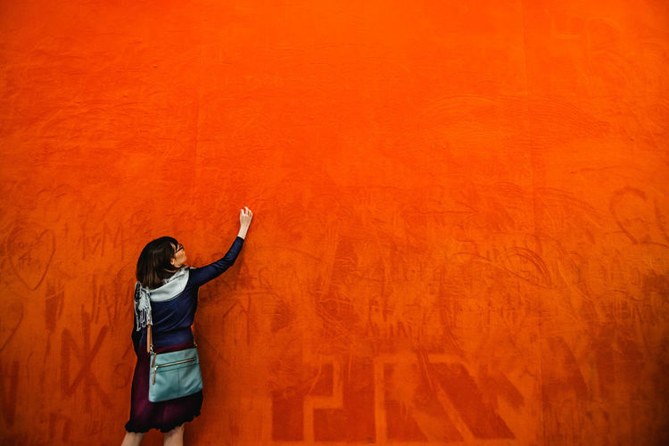Rear view of woman standing against orange wall