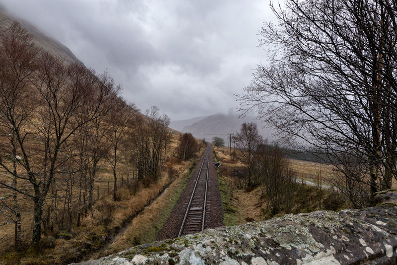 The Highland train line going off into the distant mountains Cloud - Sky Nature No People Day Sky Outdoors Tree Growth Beauty In Nature Transportation Train Line Train Tracks Highlands West Highland Way Landscape Trekking Scotland Rural Scene Travel Destinations Camping Lifestyles Leading Lines Woods Grass Hiking