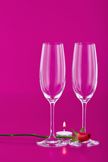 Close-up of wine glass against pink background