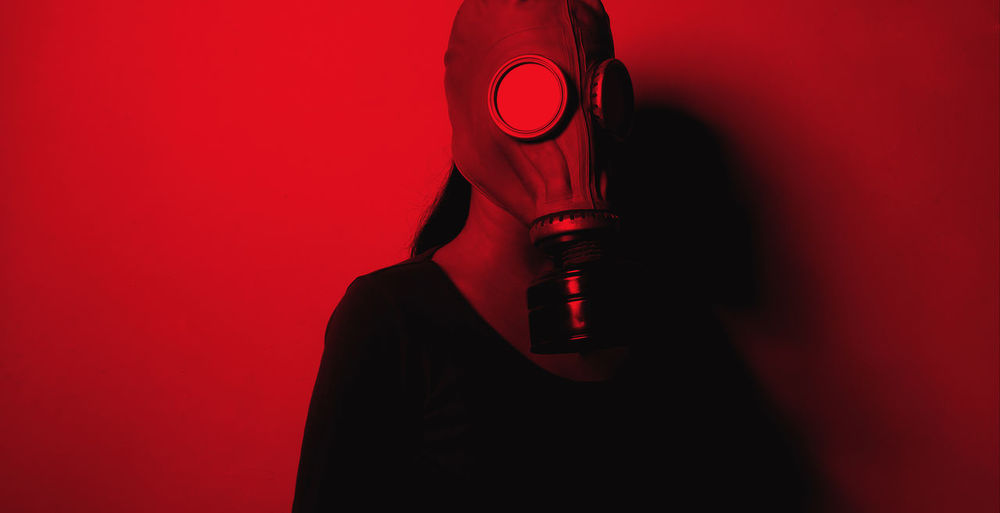 Woman wearing gas mask standing against red wall