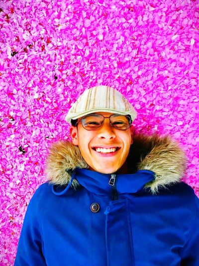 Portrait of smiling young man against pink petals