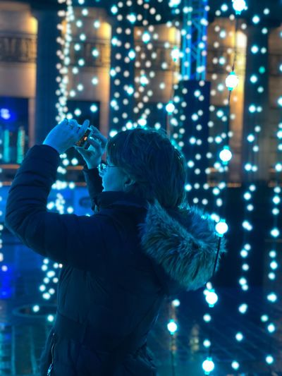 Side View Of Woman Photographing By Lights At Night