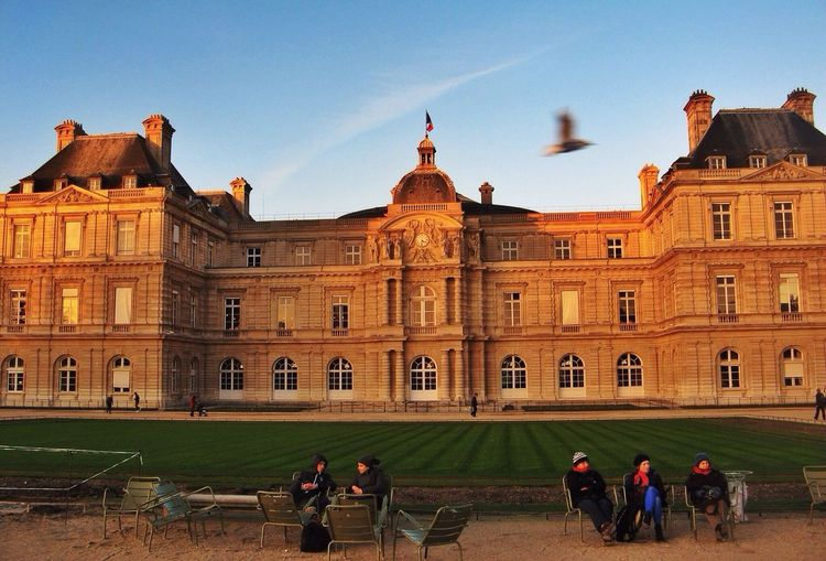 People Sitting On Chairs In Front Of Palace In Le Jardin Du Luxembourg
