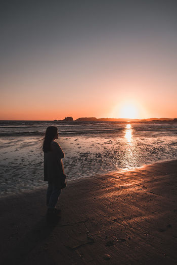 Woman Standing At Beach During Sunset