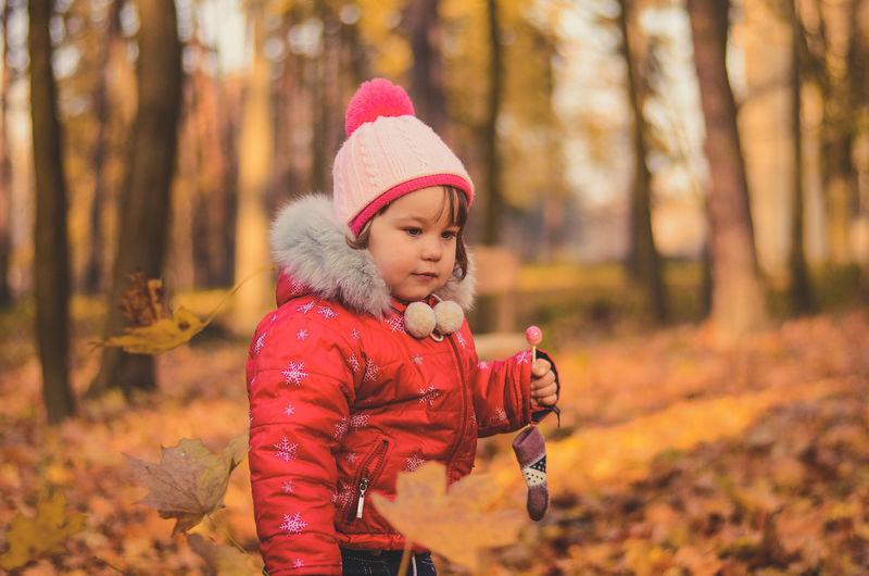 Little girl with a lollipop walks in autumn park
