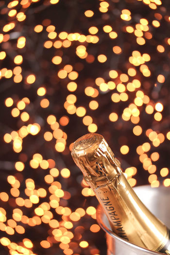 Close-up of champagne bottle in bucket against christmas lights
