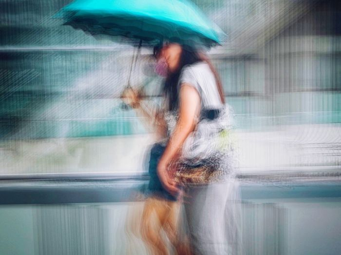 Blurred motion of man riding motorcycle on street in rainy season