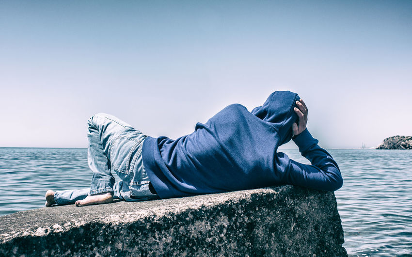 Rear view of man relaxing by sea on retaining wall