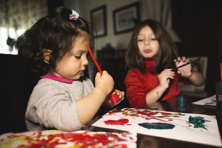 Siblings painting with watercolor paints on table at home