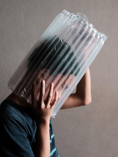 A boy head stuck in plastic wrapper