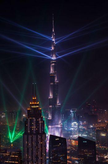 Illuminated burj khalifa in city against sky at night
