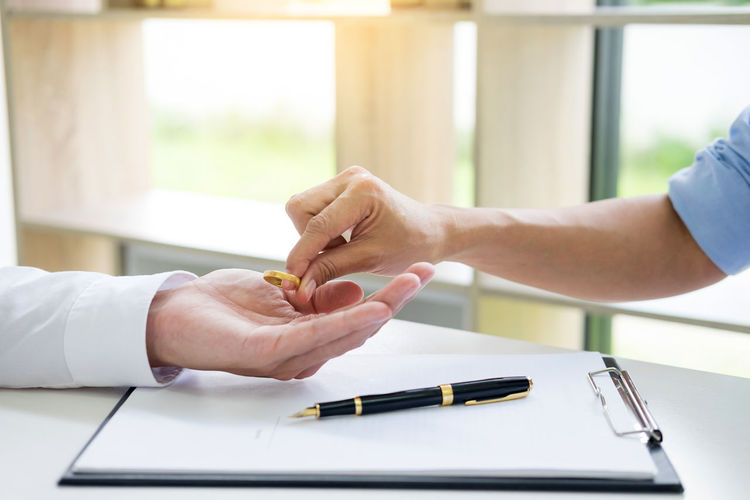 Hands Of Couple Holding Ring Over Clipboard