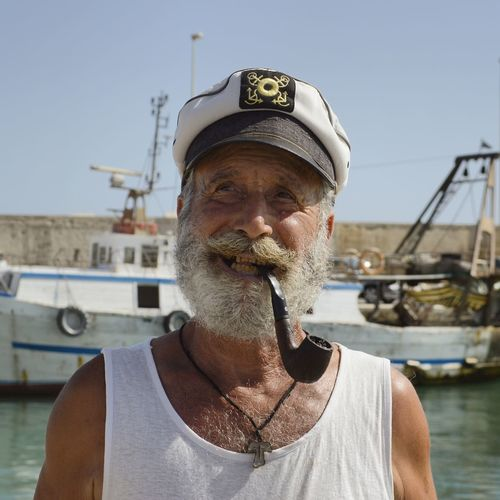 Aging In Style Pipe Beard Portrait Photography Aged Week On Eyeem EyeEm Selects Nautical Vessel Water Portrait Men Headshot Clear Sky Headwear Front View Individuality Sky Fisherman Harbor Boat Captain Cigar Fishing Uniform Cap Sailor Fishing Boat Summer Exploratorium