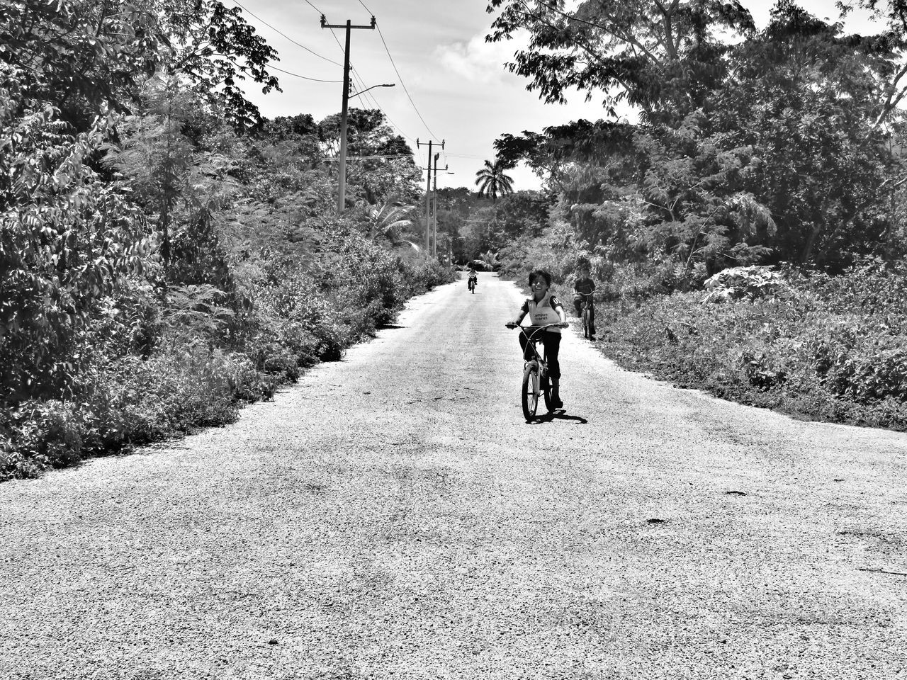 riding, real people, transportation, tree, bicycle, road, cycling, full length, day, one person, leisure activity, walking, helmet, outdoors, lifestyles, land vehicle, men, growth, nature, sky, people