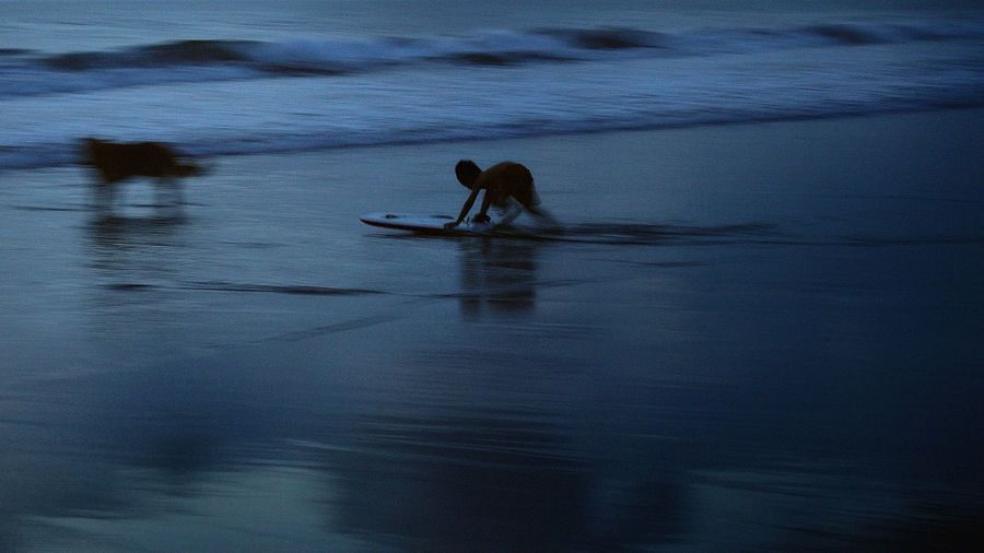 Boy surfboarding on sea at dusk
