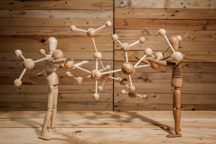 Close-up of wooden figurines holding molecular structure