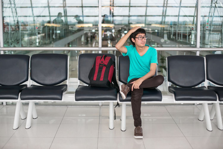 Waiting an airplane Adult Adults Only Airport Airport Waiting Asian  Business Connection Day Front View Full Length Journey One Person Outdoors People Photographer Relaxation Sitting Smiling Thai Thailand Transportation Travel Waiting Young Adult