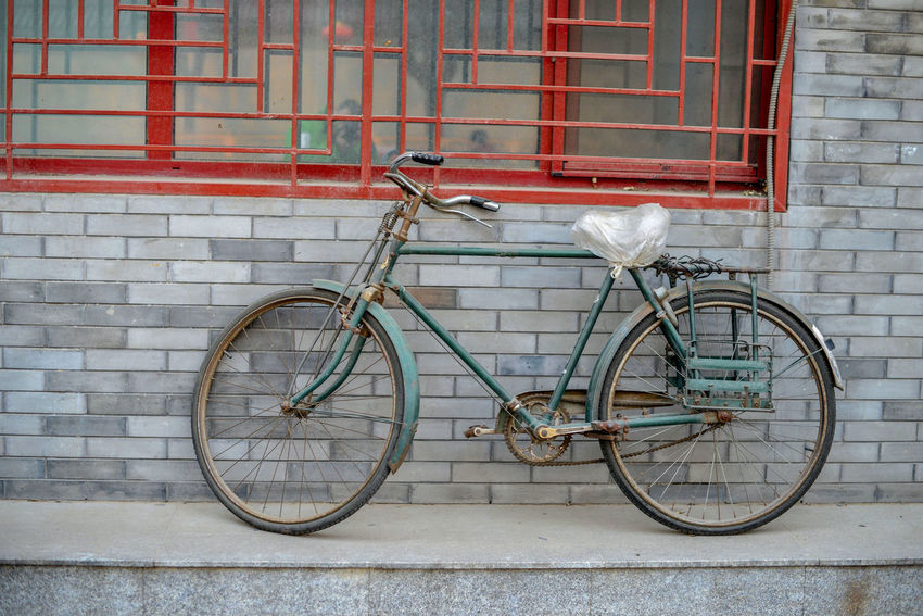 BEIJING, CHINA At the brick wall of the building is an old bike. ASIA Asian  Beijing Beijing, China City Exotica Lifestyle Rickshaw Run Road Tourists Transportation Bicycle Capital Cities  China Destination Ecology Hutong Old Parked Ride Street Tourism Trafic Urban Vintage