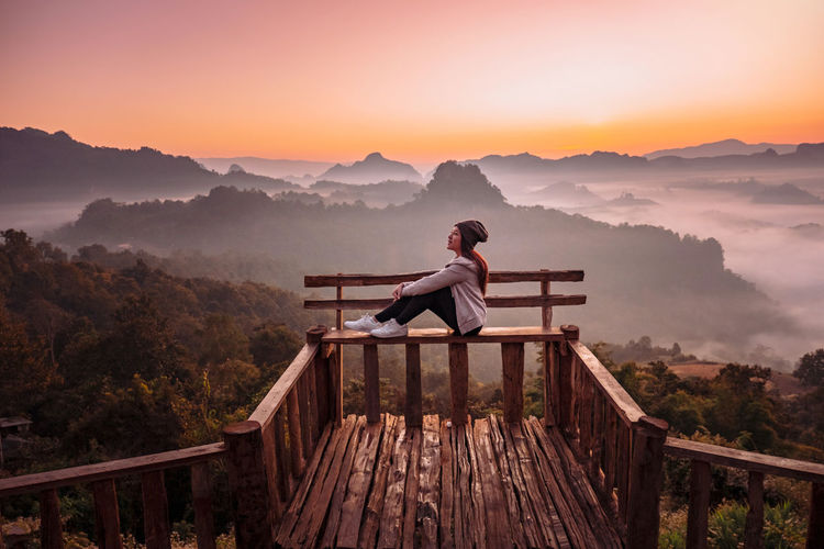 Man looking at observation point on mountain against sky during sunset