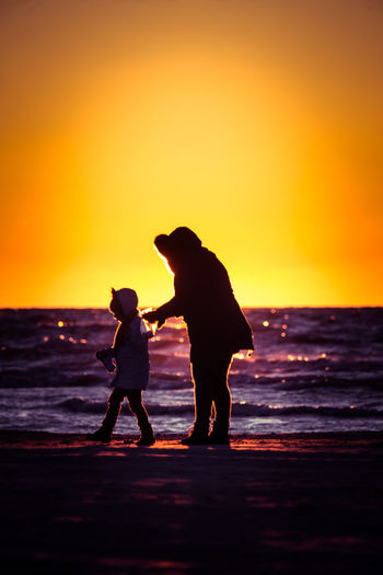 Silhouette mother and daughter beach against sky during sunset