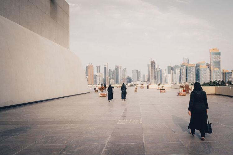 Rear view of people walking on buildings in city