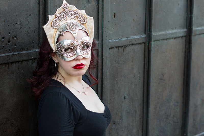 Close-Up Of Woman Wearing Venetian Mask Against Wall