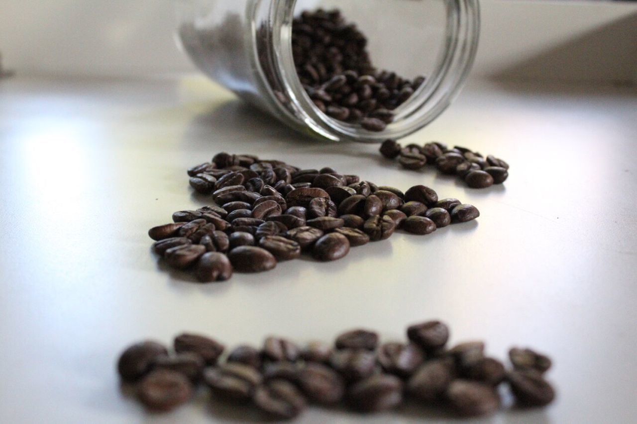 roasted coffee bean, coffee bean, food and drink, raw coffee bean, still life, freshness, coffee - drink, table, black peppercorn, indoors, ground coffee, food, coffee cup, close-up, roasted, selective focus, brown, scented, no people, ingredient, refreshment, jar, large group of objects, day