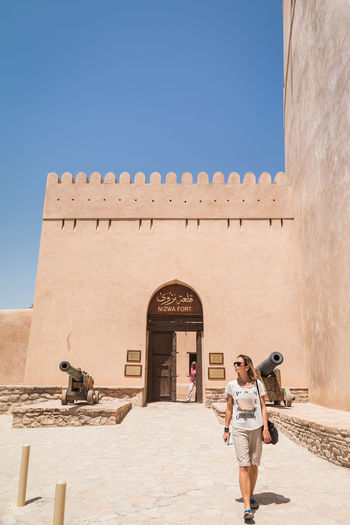 Ancient Architecture Building Exterior Built Structure Casual Clothing Clear Sky History Nizwa Fort Oman One Person Outdoors Standing Tourism Travel Travel Travel Destinations Travel Photography Vacations Walking Young Adult Young Women