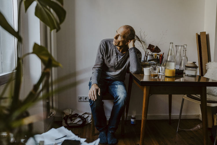 Man looking away while sitting on table at home