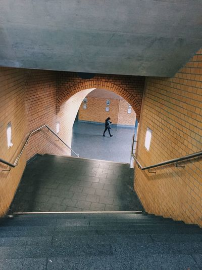 High Angle View Of Person Walking In Corridor Seen From Staircase
