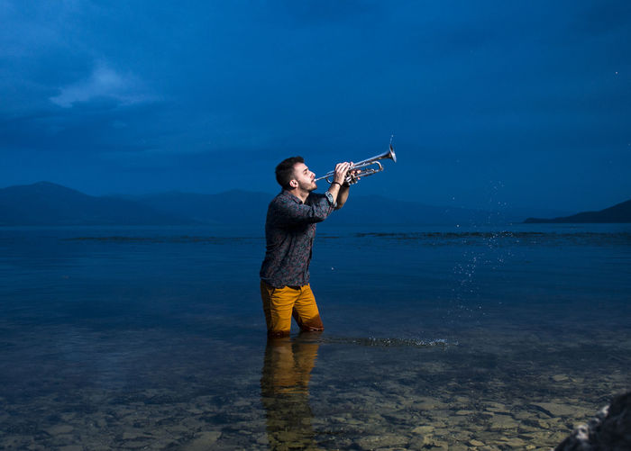 Young man playing musical instrument in sea at dusk