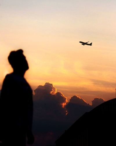 Silhouette man watching airplane flying against sky during sunset