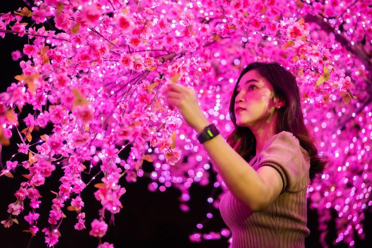 Beautiful woman standing against illuminated tree at night