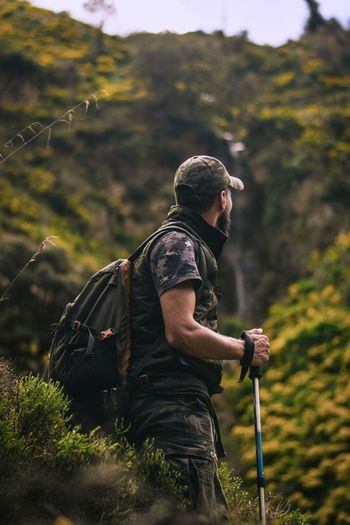 Side view of man with backpack standing in forest
