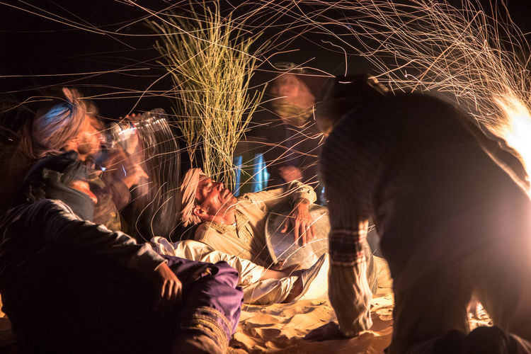 Saharan nights Night Group Of People Illuminated Women Real People Men Arts Culture And Entertainment People Adult Lifestyles Blurred Motion Motion Togetherness Event Drink Celebration Medium Group Of People Burning Emotion Glowing Glass Sparks Firework - Man Made Object Sahara Desert 2018 In One Photograph My Best Photo