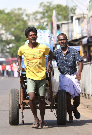 The Hard Work Of Porters Colombo Day Dilivery Full Length Lifestyles Load Looking At Camera Mode Of Transport Porter Portero Smiling Street Transportation