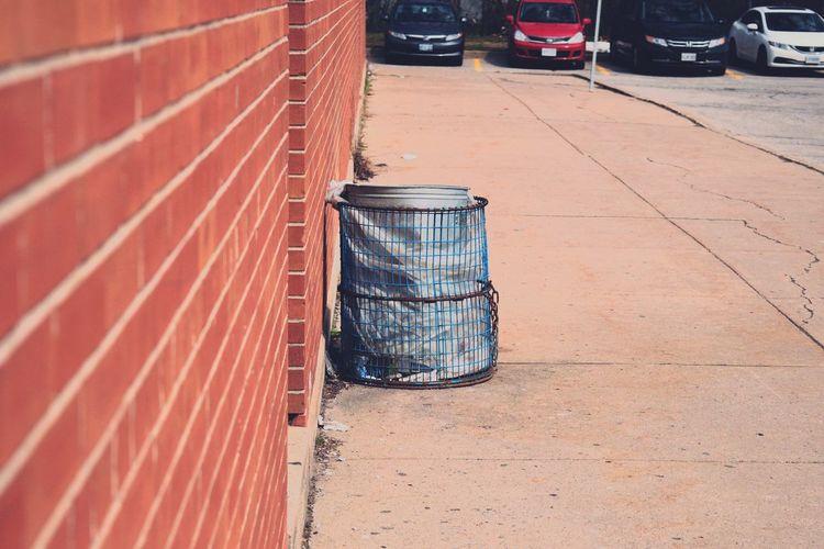 Garbage can on sidewalk against cars