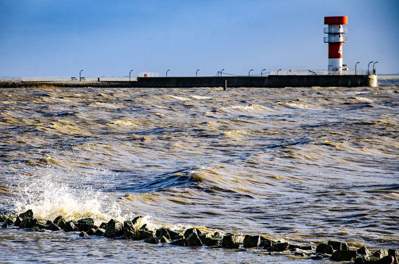 Lighthouse on pier in sea against sky