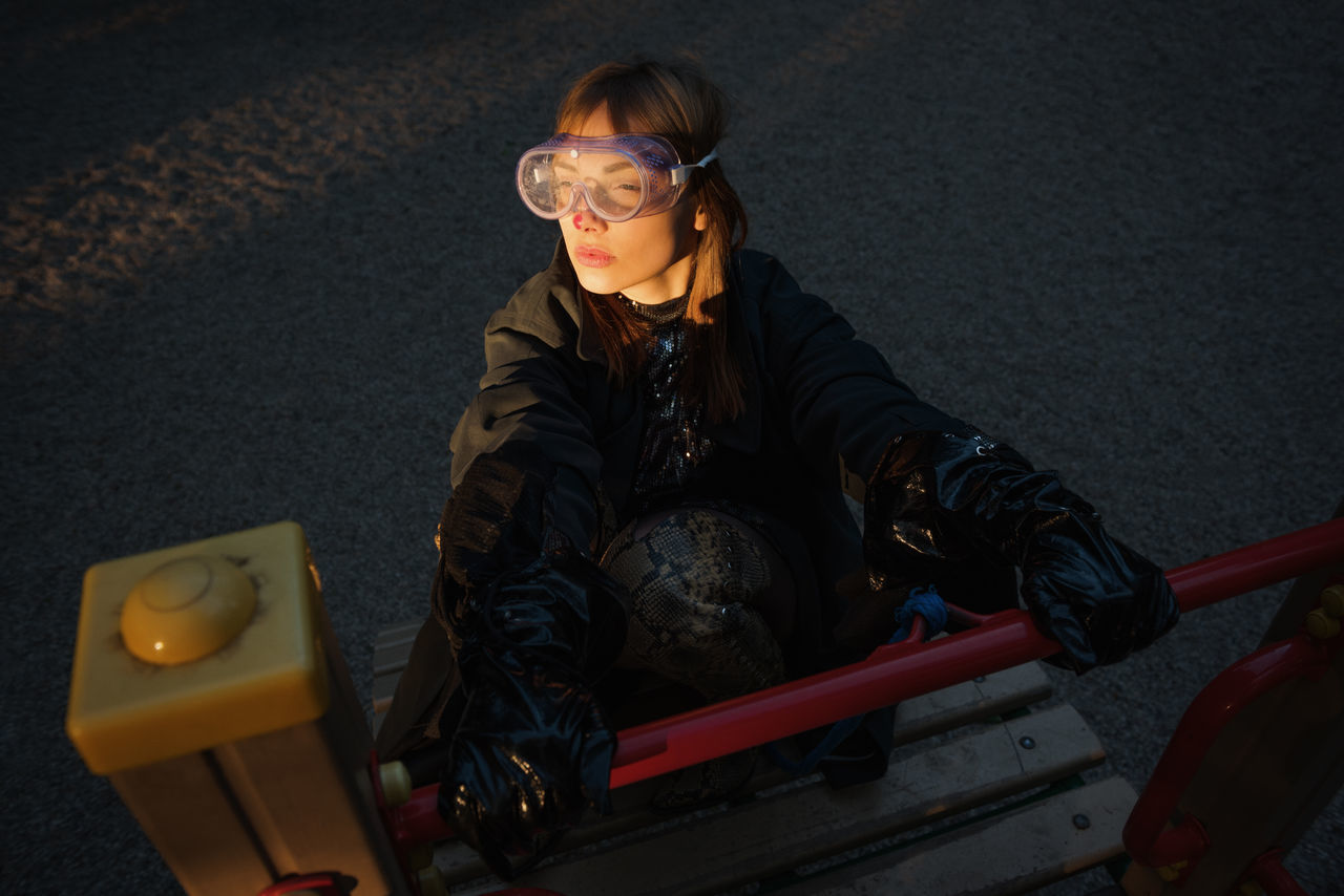 High angle view of woman wearing eyewear while sitting in playground