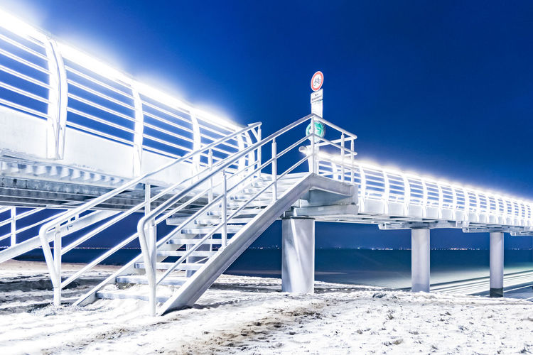 Low angle view of illuminated bridge over sea against clear blue sky at night